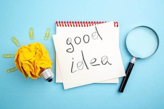 Vue de dessus bonne idée écrite sur papier idée concept d'ampoule avec du papier froissé et des clips de gemme lupa sur table