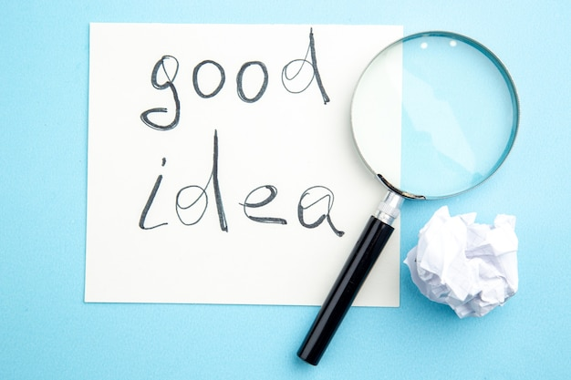 Vue de dessus bonne idée écrite sur papier lupa sur table