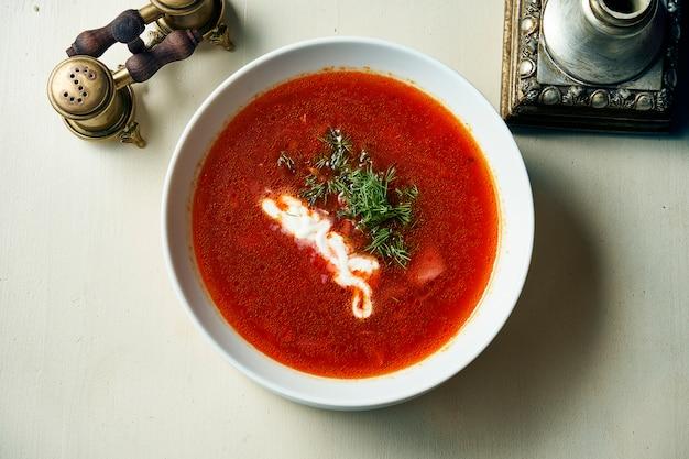 Vue de dessus borscht, soupe aigre de la cuisine ukrainienne, avec viande, pomme de terre, betteraves. table de nourriture. soupe rouge dans un bol avec pour la conception. photo pour le menu