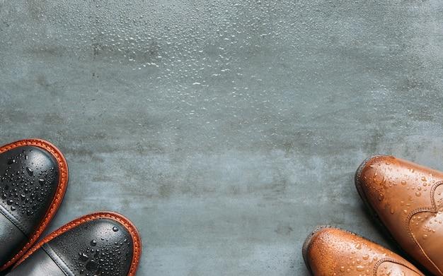 Vue de dessus des bottes pour hommes en cuir noir et marron avec des gouttes d'eau sur fond bleu marine grunge humide, copie espace