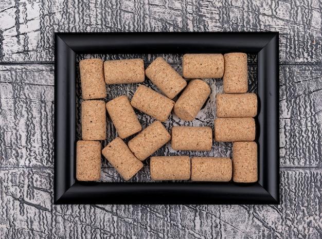 Vue de dessus des bouchons en liège dans un cadre noir sur pierre blanche horizontale