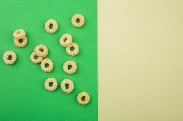 Vue de dessus de la boucle et des céréales saines sur la surface verte et fond jaune