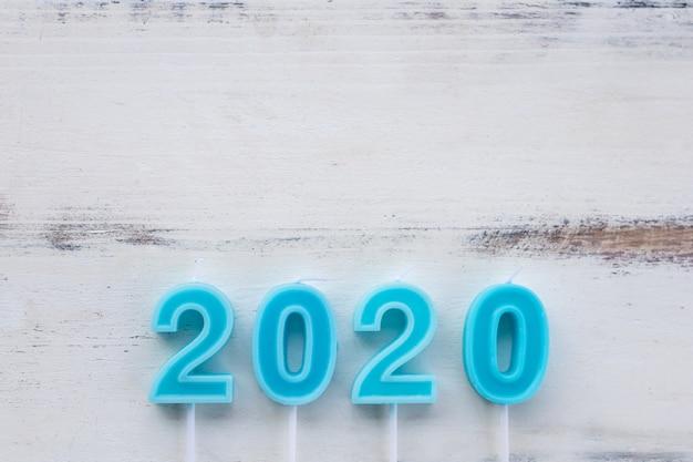 Vue de dessus de bougie bleu clair numéro 2020 sur planche de bois blanc avec espace de copie.