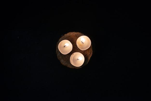 Vue de dessus des bougies allumées sur un mur sombre