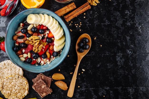 Vue de dessus de la bouillie d'avoine avec des fraises, des bleuets, des bananes, des fruits secs et des noix dans un bol en céramique et une cuillère en bois avec des baies sur fond noir avec copie espace