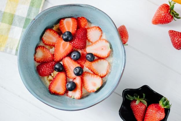 Vue de dessus de la bouillie d'avoine avec des fraises et des bleuets en tranches dans un bol en céramique et de l'avoine pendant la nuit dans un bocal en verre sur la table