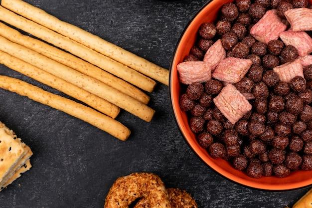 Vue de dessus des boules de céréales dans une assiette et des bâtonnets de pain sur une surface sombre