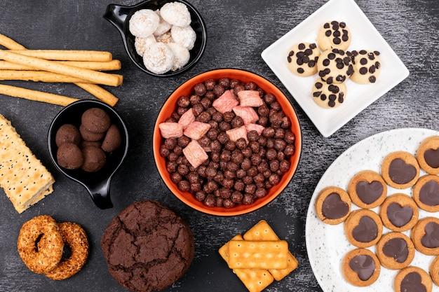 Vue de dessus des boules de céréales avec différents cookies sur une surface sombre