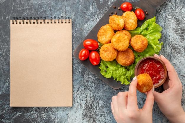 Vue de dessus des boules de fromage frites sur un bol de ketchup de bloc-notes de planche à découper dans une main féminine