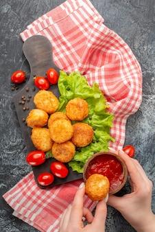 Vue de dessus des boules de fromage frites sur une planche à découper un bol de ketchup et une boule de fromage dans les mains de la femme