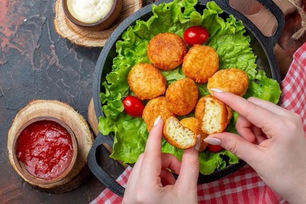 Vue de dessus des boules de fromage et des sauces dans une casserole sur une surface sombre