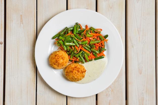 Vue de dessus des boulettes de viande panées servies avec des haricots verts et des carottes épicées