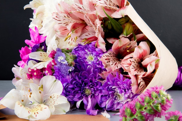 Vue de dessus d'un bouquet d'alstroemeria de couleur blanche et rose et de fleurs de chrysanthème en papier kraft sur fond sombre