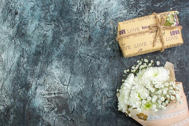 Vue de dessus bouquet de fleurs cadeau enveloppé sur fond sombre avec lieu de copie