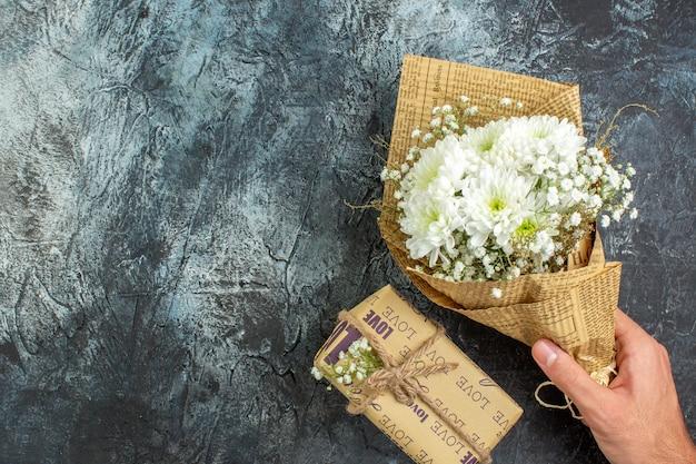 Vue de dessus bouquet de fleurs en cadeau de main féminine sur fond sombre copie place
