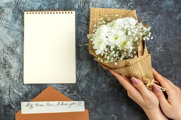 Vue de dessus bouquet de fleurs dans les mains des femmes love letter notebook sur fond sombre