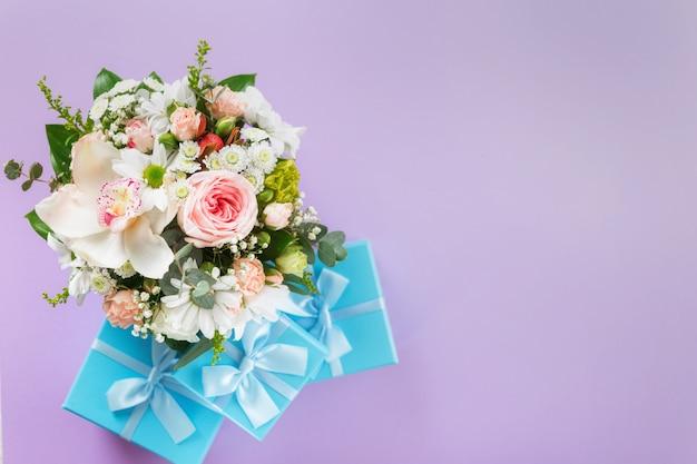 Vue de dessus bouquet de fleurs sur fond violet avec des coffrets cadeaux copie espace plat poser