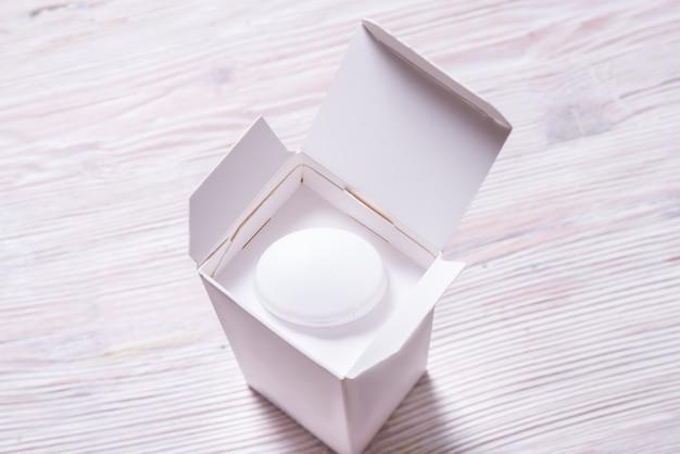 Vue de dessus, bouteille de crème blanche à l'intérieur du carton cox,