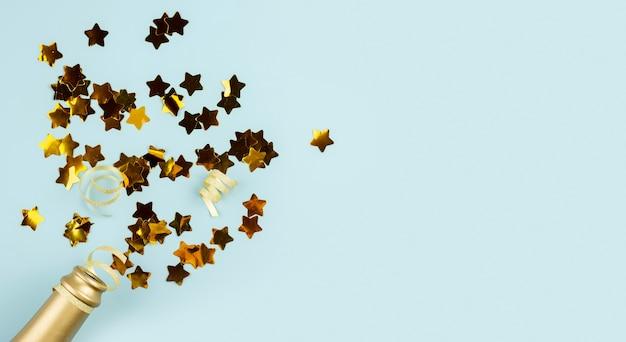 Vue de dessus bouteille et étoiles dorées