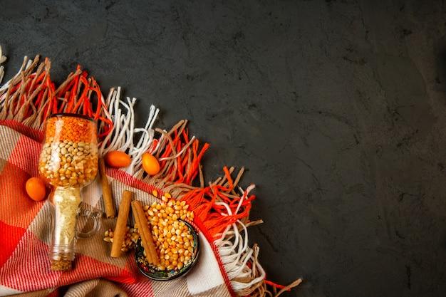 Vue de dessus d'une bouteille avec des graines de maïs et des haricots crus kumquats et bâton de cannelle sur un plaid avec pompon avec copie espace sur fond noir