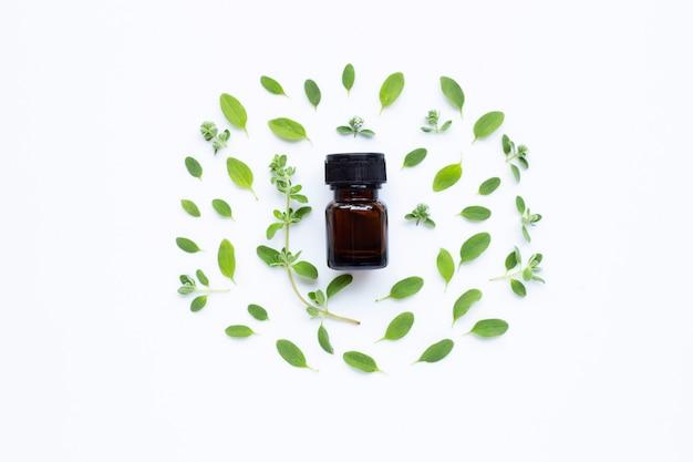 Vue de dessus. bouteille d'huile essentielle de marjolaine sur blanc