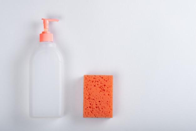 Vue de dessus bouteille ménagère en plastique blanc avec distributeur, éponge orange sur fond blanc avec espace de copie