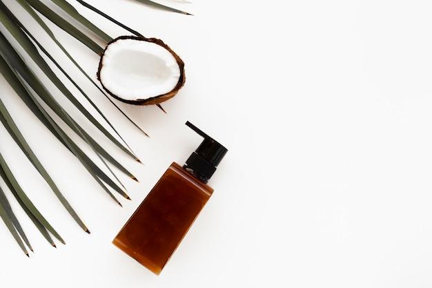 Vue de dessus de la bouteille de noix de coco et d'huile essentielle avec espace de copie