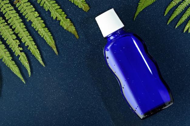 Vue de dessus bouteille en verre bleu avec couvercle blanc sur fond bleu avec des feuilles de fougère et de l'espace de copie