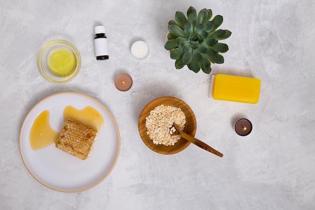Une vue de dessus des bouteilles d'huile essentielle; l'avoine; plante de cactus; savon jaune et nid d'abeille sur fond de béton