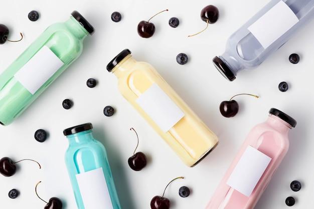 Vue de dessus des bouteilles de jus de fruits multicolores avec des myrtilles et des cerises