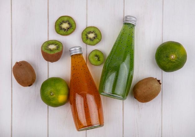 Vue de dessus des bouteilles de jus avec des mandarines et des kiwis sur un mur blanc