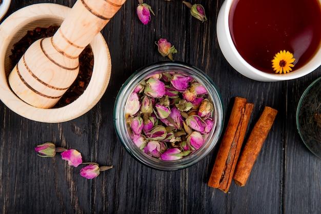 Vue de dessus des boutons de rose secs dans un bocal en verre avec des bâtons de cannelle et un mortier en bois rempli de grains de poivre noir et une tasse de thé sur du bois noir