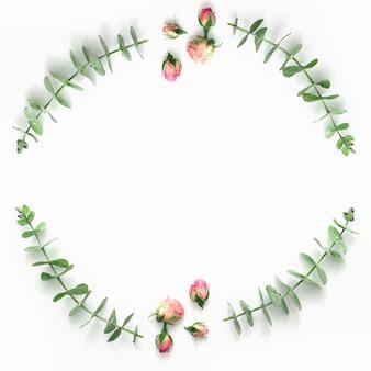 Vue de dessus des boutons de roses roses et eucalyptus sur une surface blanche