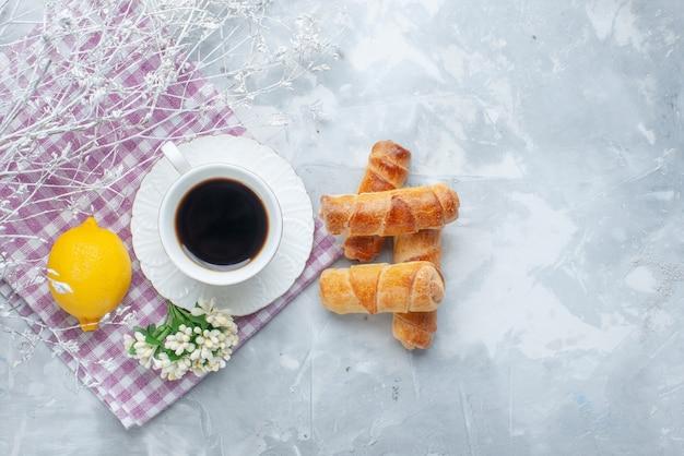 Vue de dessus bracelets sucrés avec remplissage avec café et citron sur le fond clair pâtisserie cuire café sucré
