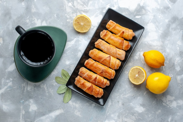 Vue de dessus des bracelets sucrés avec tasse de thé au citron sur la table lumineuse, gâteau pâtisserie cuire le sucre sucré