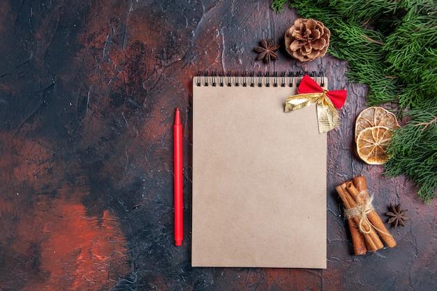 Vue de dessus des branches d'arbres de pin et de pommes de pin un cahier stylo rouge anis cannelle sur l'espace libre de surface rouge foncé
