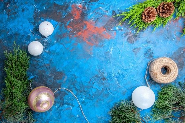 Vue de dessus des branches de pin cônes fil de paille boules d'arbre de noël sur une surface bleu-rouge