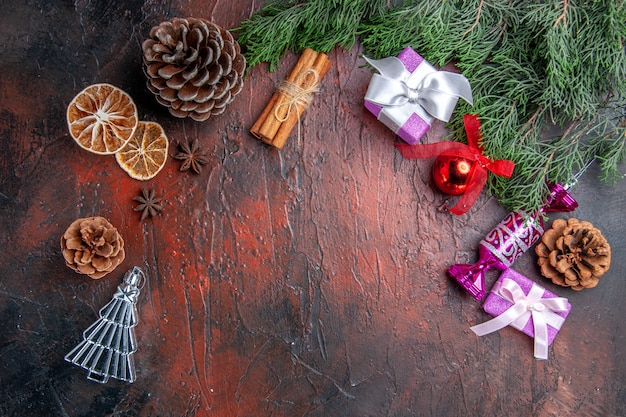 Vue de dessus des branches de pin avec des cônes jouets d'arbre de noël tranches de citron séchées à la cannelle anis étoilés sur fond rouge foncé espace libre photo du nouvel an