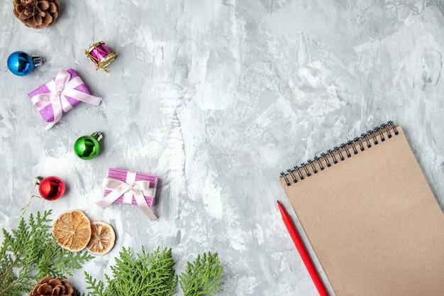 Vue de dessus des branches de pin petits cadeaux jouets d'arbre de noël crayon pour ordinateur portable sur une surface grise
