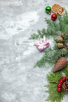 Vue de dessus des branches de pin petits cadeaux jouets d'arbre de noël sur une surface grise