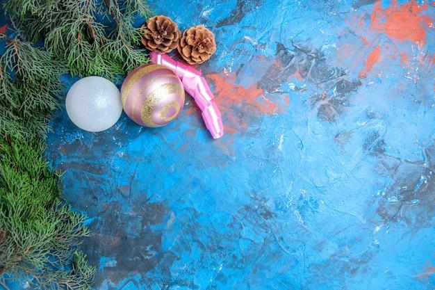 Vue de dessus des branches de pin pommes de pin boules d'arbre de noël sur une surface bleu-rouge