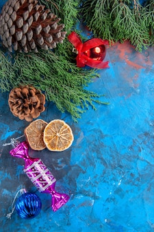 Vue de dessus branches de pin pommes de pin jouets d'arbre de noël tranches de citron séchées sur une surface bleu-rouge
