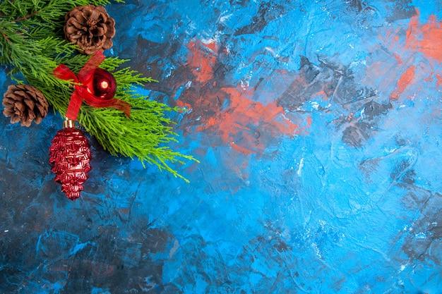 Vue de dessus des branches de pin avec des pommes de pin et des ornements suspendus sur fond bleu-rouge avec place libre
