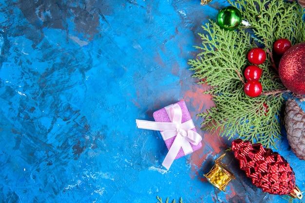 Vue de dessus branches de sapin branches de sapin cônes jouets d'arbre de noël sur fond bleu