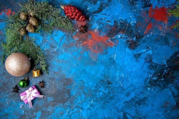 Vue de dessus des branches de sapin cônes jouets d'arbre de noël sur fond bleu