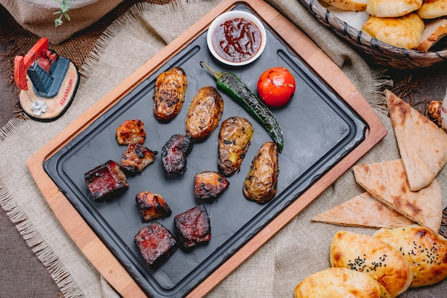 Vue de dessus brochette de foie de boeuf avec pommes de terre et tomates au poivron vert grillé et sauce sur un plateau