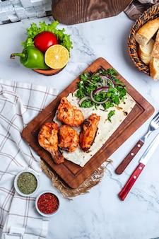 Vue de dessus de brochette de poulet aux herbes et oignons rouges sur lavash sur planche de bois servi avec des légumes frais et des épices sur la table