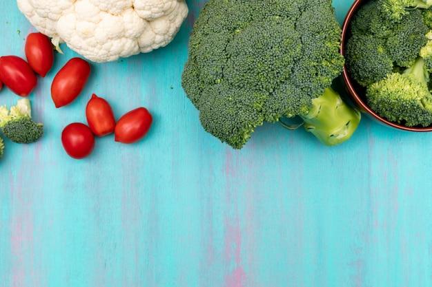 Vue de dessus de brocoli de chou-fleur et tomate cerise avec copie espace sur la surface bleue