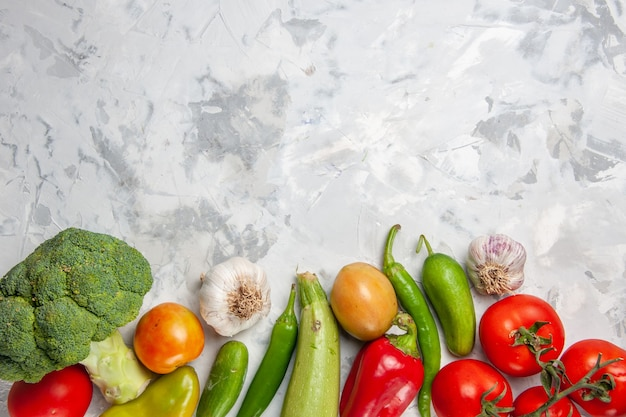 Vue de dessus brocoli vert frais avec des légumes sur le sol blanc salade régime santé mûr