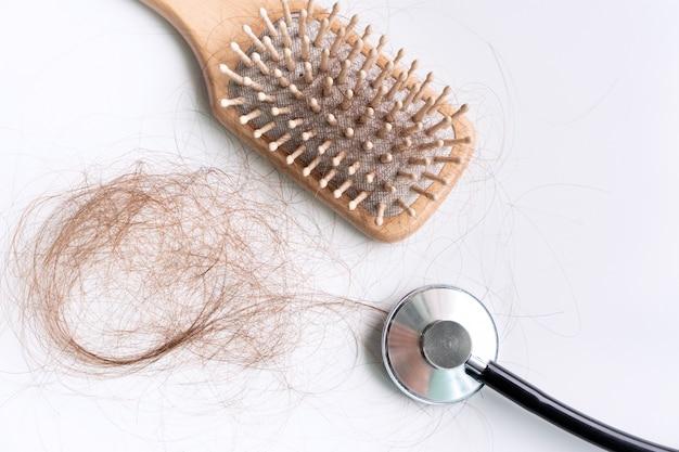 Vue de dessus d'une brosse avec des cheveux perdus dessus et un stéthoscope médical